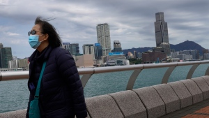 A woman wearing a face mask walks at the waterfront against the Victoria Habour in Hong Kong Sunday, Feb. 16, 2020.  (AP Photo/Vincent Yu)