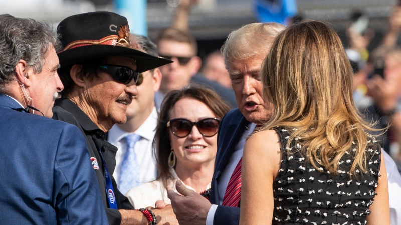U.S. President Donald Trump and first lady Melania Trump greet racing legend Richard Petty, second from left, at the NASCAR Daytona 500 auto race at Daytona International Speedway, Sunday, Feb. 16, 2020, in Daytona Beach, Fla. (AP Photo/Alex Brandon)