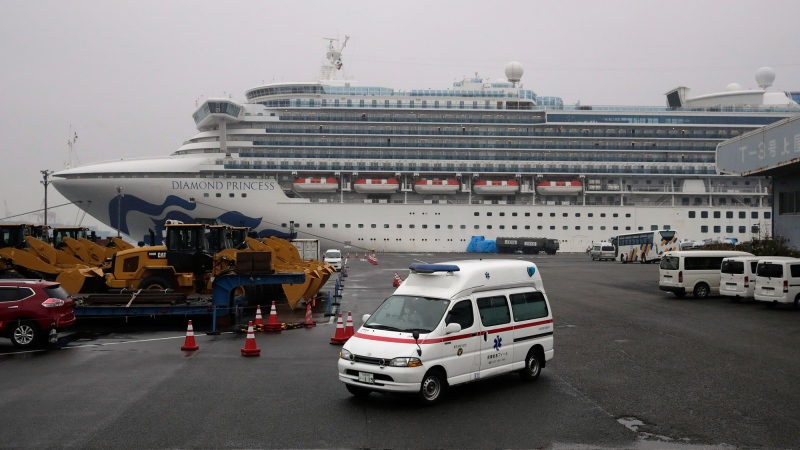 An ambulance leaves a port where the quarantined Diamond Princess cruise ship is docked Sunday, Feb. 16, 2020, in Yokohama, near Tokyo. The U.S. says Americans aboard the quarantined ship will be flown back home on a chartered flight Sunday, but that they will face another two-week quarantine. (AP Photo/Jae C. Hong)
