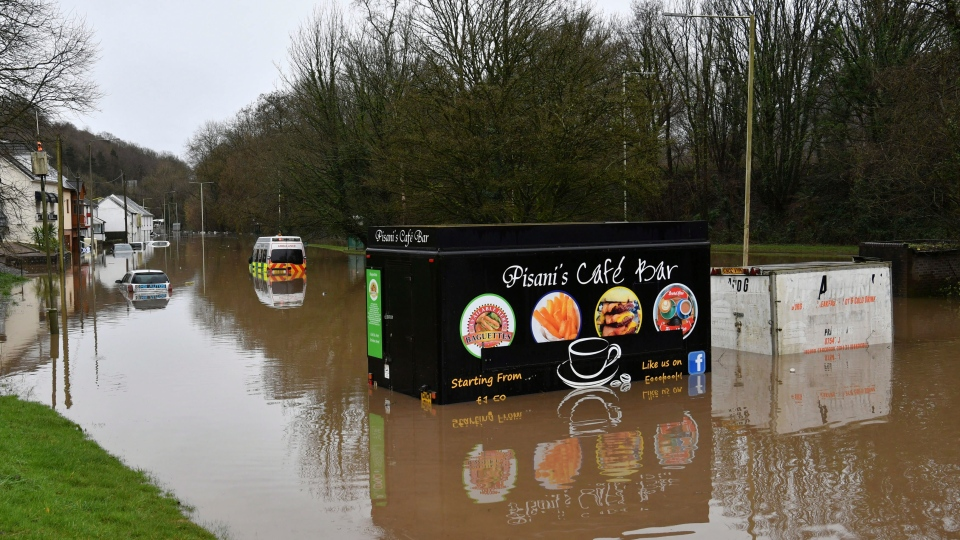 "A half submerged fast food van after flooding, in Nantgarw, Wales, Sunday Feb. 16, 2020. Storm Dennis is roaring across Britain with high winds and heavy rains, prompting authorities to issue 350 flood warnings, including a ""red warning"