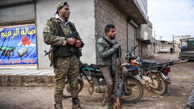 Syrian rebels sit outside Idlib, Syria, Saturday, Feb. 15, 2020. Syrian troops are waging an offensive in the last rebel stronghold. (AP Photo)