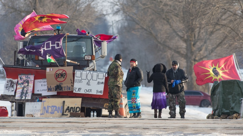 People talk at a rail blockade on the eleventh day of demonstration in Tyendinaga, near Belleville, Ont., Sunday, Feb. 16, 2020. The protest is in solidarity with the Wet'suwet'en hereditary chiefs opposed to the LNG pipeline in northern British Columbia. THE CANADIAN PRESS/Lars Hagberg