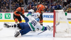 Vancouver Canucks goalie Thatcher Demko (35) dives across the crease as Troy Stecher (51) stops Anaheim Ducks' Nick Ritchie (37) while Adam Henrique (14) watches during the third period of an NHL hockey game in Vancouver, on Sunday February 16, 2020. THE CANADIAN PRESS/Darryl Dyck