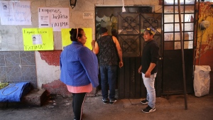 Neighbours and relatives wait outside the home of Fatima, a 7-year-old girl who was abducted from the entrance of a primary school and later murdered, in Mexico City, Monday, Feb. 17, 2020.  (AP Photo/Marco Ugarte)