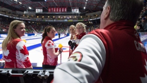 From left to right, Team Canada skip Chelsea Carey, lead Rachel Brown, second Dana Ferguson and third Sarah Wilkes speak to coach Dan Carey prior to the fourth draw against Saskatchewan at the Scotties Tournament of Hearts curling championship in Moose Jaw, Saskatchewan, Sunday, Feb. 16, 2020. (Jonathan Hayward/The Canadian Press via AP)