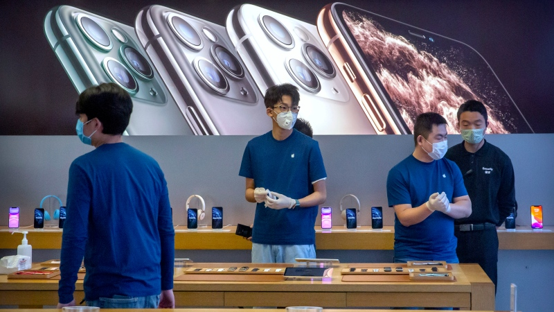 In a Feb. 14, 2020 file photo, employees wear face masks as they stand in a reopened Apple Store in Beijing. (AP Photo/Mark Schiefelbein, File)