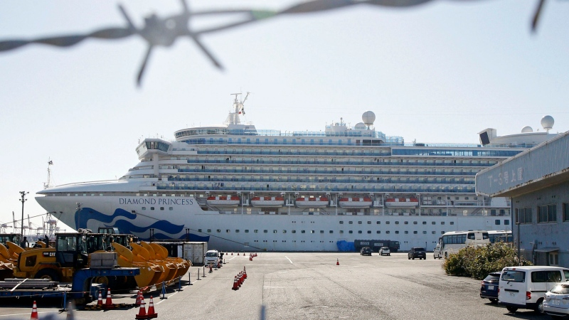 The quarantined ship Diamond Princess is pictured through barbed wire at Yokohama port in Yokohama, near Tokyo Monday, Feb. 17, 2020. Japanese officials have confirmed 99 more people infected by the new virus aboard the ship, the Health Ministry said Monday. (Mayuko Isobe/Kyodo News via AP)
