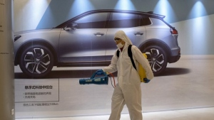 In this Feb. 12, 2020, photo, a worker disinfects a mall near an advertisement for a car in Beijing, China. (AP Photo/Ng Han Guan)