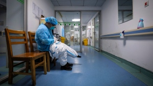 In this Sunday, Feb. 16, 2020, photo, a doctor puts on a protective suit as he prepares to check on the patients at Jinyintan Hospital designated for new coronavirus infected patients, in Wuhan in central China's Hubei province. (Chinatopix via AP)