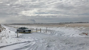 An RCMP unit and police tape near the intersection of Range Road 290 and Township Road 264, southeast of Airdrie, following the discovery of a body