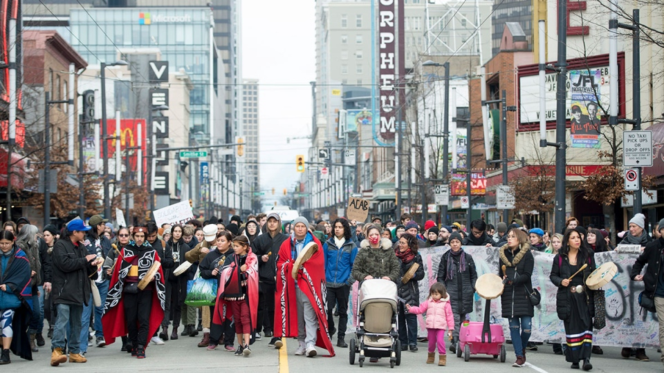 Protesters walk down Granville Street in downtown Vancouver, Wednesday, Feb. 12, 2020. (Jonathan Hayward / THE CANADIAN PRESS)