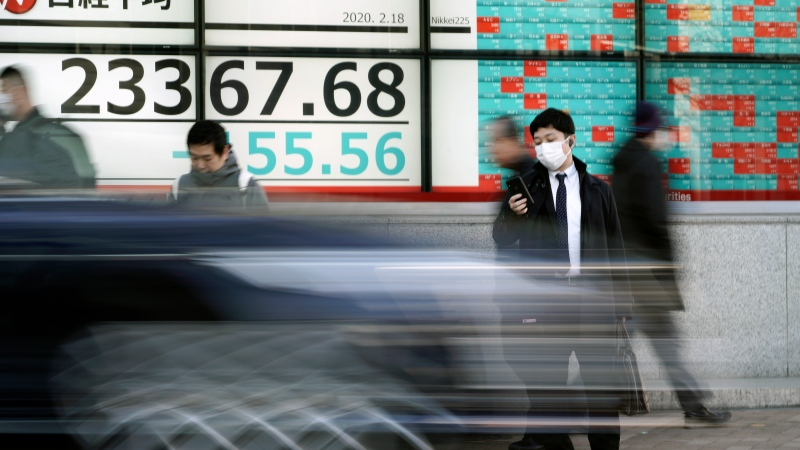 People walk past an electronic stock board showing Japan's Nikkei 225 index at a securities firm in Tokyo Tuesday, Feb. 18, 2020. (AP Photo/Eugene Hoshiko)