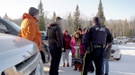 Bradley Holloway's family speak with RCMP at the site on Stoney Nakoda First Nation where remains were found.