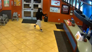A masked man attempting to rob a Kentucky chicken joint at gun point wound up fleeing the restaurant empty-handed when two married police officers on a date night chased him from the scene, authorities said. (Louisville Metro Police Department/Storyful)