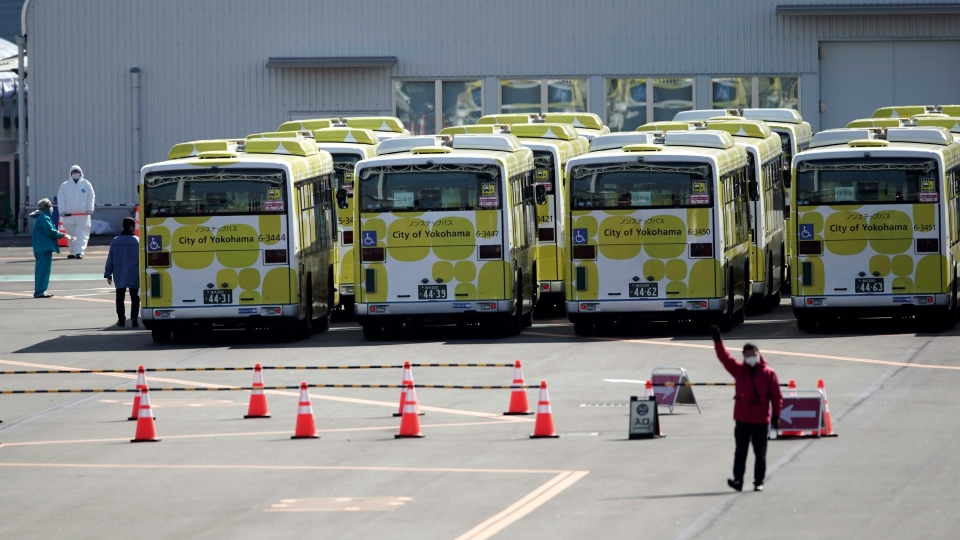 Buses for the passengers from the quarantined Diamond Princess cruise ship park a port in Yokohama, near Tokyo, Wednesday, Feb. 19, 2020. (AP Photo/Eugene Hoshiko)