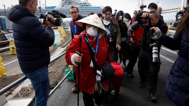 An unidentified passenger is surrounded by the media after she disembarked from the quarantined Diamond Princess cruise ship Wednesday, Feb. 19, 2020, in Yokohama, near Tokyo. (AP Photo/Jae C. Hong)