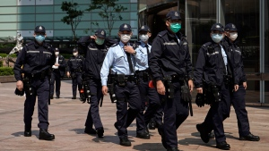 Police officers wearing masks, patrol in Central, a business district in Hong Kong, Wednesday, Feb. 19, 2020. (AP Photo/Kin Cheung)
