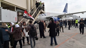 Syrian officials and journalists disembark a Syrian commercial plane after it landed at Aleppo Airport, Syria, on Feb. 19, 2020. (SANA via AP)