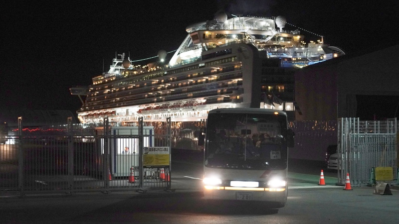 Buses carrying Australian passengers from the quarantined Diamond Princess cruise ship leave a port in Yokohama, near Tokyo, Wednesday, Feb. 19, 2020. (AP Photo/Eugene Hoshiko)