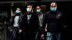 People wearing masks, walk in Central, a business district in Hong Kong, Wednesday, Feb. 19, 2020. (AP Photo/Kin Cheung)