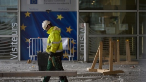 A construction worker stands in front of a door with the EU stars at EU headquarters in Brussels, on Oct. 9, 2019. (Virginia Mayo / AP)