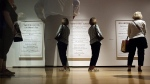 ArtPrize-goers are reflected in glass as they look at Kenneth Lum's entry, 'Three Women: the Crusader, the Tattooed Lady and the Keypunch Operator,' at the Grand Rapids, Mich., Art Museum on Wednesday, Sept. 21, 2016.  (Cory Morse / The Grand Rapids Press-M-Live via AP)