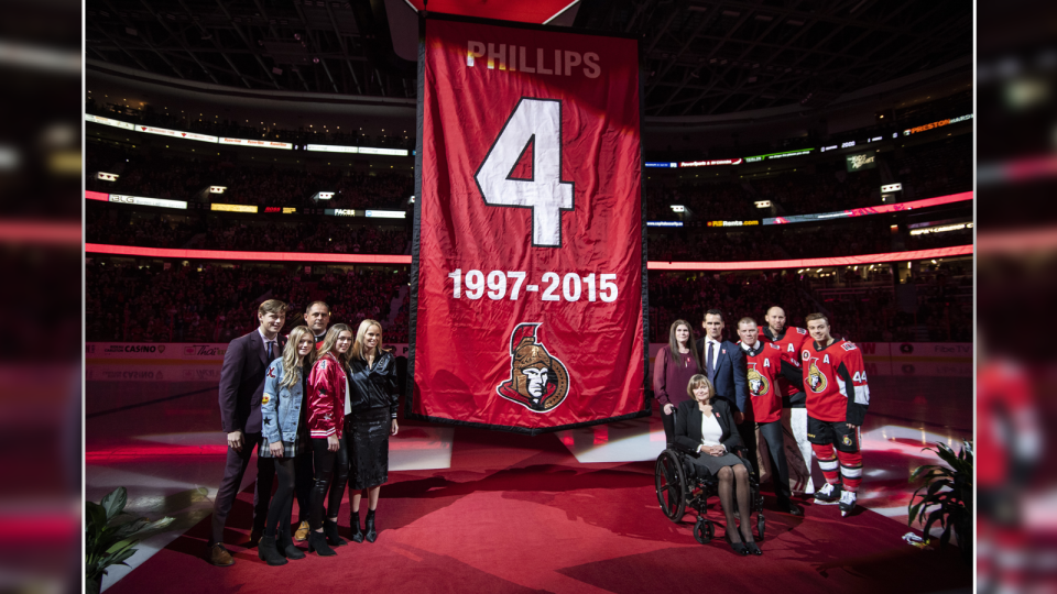 Retired Ottawa Senators player Chris Phillips gathers with family members and teammates beside a banner with jersey number before it is raised to the rafters at a ceremony marking the retirement of his jersey number before a game between the Senators and the Buffalo Sabres in Ottawa, Tuesday, Feb. 18, 2020. (Justin Tang/THE CANADIAN PRESS)