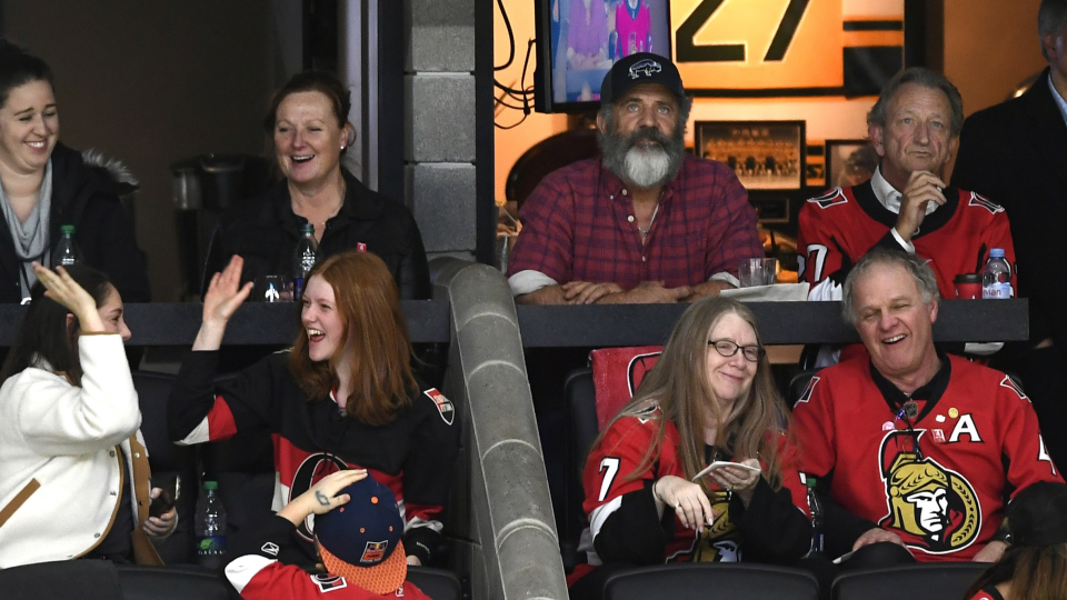 Actor Mel Gibson, second from right in top row, and Ottawa Senators owner Eugene Melnyk, right, watch the Senators and Buffalo Sabres in NHL hockey action in Ottawa, Tuesday, Feb. 18, 2020. (Justin Tang/THE CANADIAN PRESS)