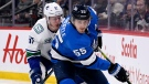 Winnipeg Jets' Mark Scheifele (55) carries the puck past Vancouver Canucks' Tyler Myers (57) during second period NHL action in Winnipeg on Tuesday Jan. 14, 2020. THE CANADIAN PRESS/Fred Greenslade