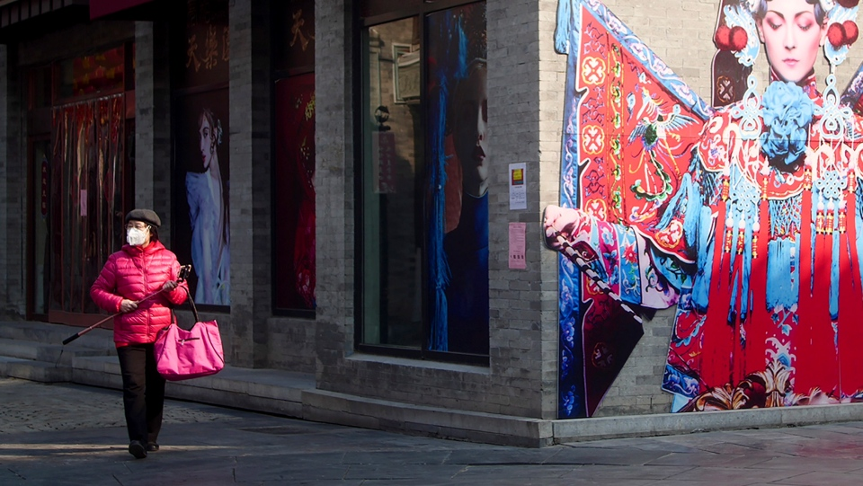 A woman wears a mask as she strolls through a quiet retail street in Beijing, China on Wednesday, Feb. 19, 2020. (AP Photo/Sam McNeil)