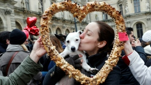 True love: a woman and her Valentine's Day date pose behind a heart-shaped pastry during a February 14 Paris flash mob. (AFP)