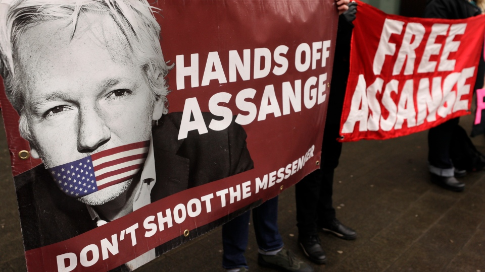 Demonstrators hold banners outside Westminster Magistrates Court in London, Wednesday, Feb. 19, 2020. (AP Photo/Kirsty Wigglesworth)