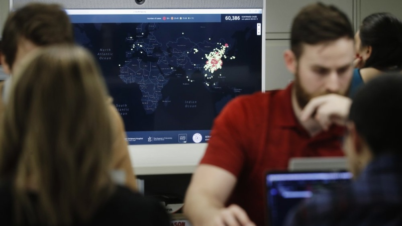 In this Thursday, Feb. 13, 2020 photo, Kyle Martin, a worker at HealthMap, a system using artificial intelligence to monitor global disease outbreaks, mines health data to keep the system up to date in a work area at Boston Children's Hospital in Boston. (AP Photo/Steven Senne)