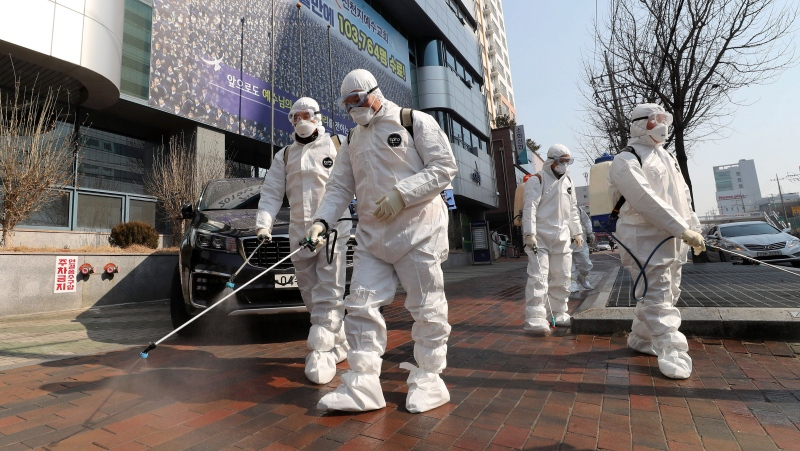 Workers wearing protective gears spray disinfectant against the new coronavirus in front of a church in Daegu, South Korea, Thursday, Feb. 20, 2020. (Kim Jun-beom/Yonhap via AP)