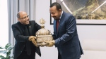 Ethiopia's Prime Minister, Abiy Ahmed, right, with gloved hands as he officially hands over a crown to the country's tourism minister, Hirut Kassaw, on Feb. 20, 2020. (The Office of Prime Minister Abiy Ahmed via AP)