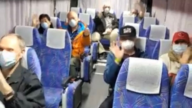 Canadian cruise passengers wait on board a bus in Yokohama, Japan to take them to an airport in Tokyo.