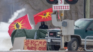 A protester stands between Mohawk Warrior Society flags at a rail blockade on the tenth day of demonstration in Tyendinaga, near Belleville, Ont., Sunday, Feb. 16, 2020. The protest is in solidarity with the Wet'suwet'en hereditary chiefs opposed to the LNG pipeline in northern British Columbia. THE CANADIAN PRESS/Lars Hagberg