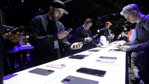 People look at different Samsung Galaxy S20 5G phones displayed at the Unpacked 2020 event in San Francisco, Tuesday, Feb. 11, 2020. (AP Photo/Jeff Chiu)