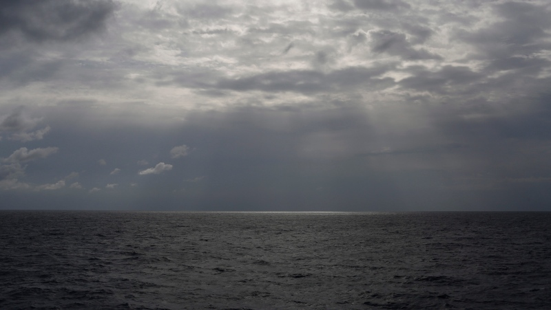In this Sunday, Sept. 8, 2019 file photo the sun pierces the clouds over international waters north of Libya in the Mediterranean Sea. A rubber dinghy packed with 91 migrants that set out from Libyan shores in hopes of reaching Europe has apparently gone missing in the Mediterranean, the UN refugee agency said Thursday, Feb. 20, 2020. (AP Photo/Renata Brito, File)