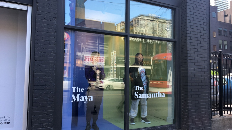 Models pose at a Toronto store front window to simulate how victims are seen as profitable items.