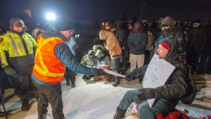 Police serve an injunction to protesters at a rail blockade in St-Lambert, south of Montreal, Que. on Thursday, February 20, 2020. The protesters are blocking the line in solidarity with the Wet'suwet'en hereditary chiefs opposed to the LNG pipeline in northern British Columbia. THE CANADIAN PRESS/Ryan Remiorz