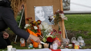 In this Dec. 12, 2018, file photo, a woman lights candles during a candlelight vigil for murdered British tourist Grace Millane at Cathedral Square in Christchurch, New Zealand. At a sentencing hearing at the Auckland High Court on Friday Feb. 21, 2020, the killer, who has name suppression, has been sentenced to life imprisonment with a minimum non-parole period of 17 years. (AP Photo/Mark Baker, File)