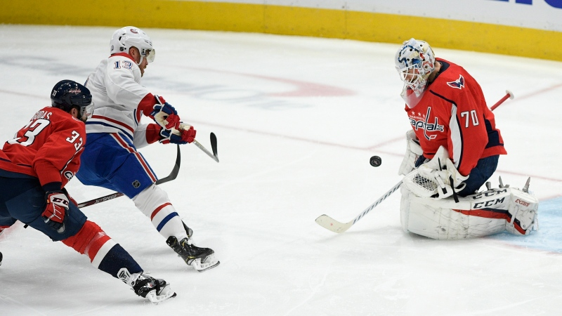 Washington Capitals goaltender Braden Holtby (70) stops the puck against Montreal Canadiens center Max Domi (13) during the first period of an NHL hockey game, Thursday, Feb. 20, 2020, in Washington. Also seen is Capitals defenseman Radko Gudas (33). (AP Photo/Nick Wass)