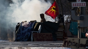A protesters stand beside smoke at the closed train tracks in Tyendinaga Mohawk Territory near Belleville, Ont., on Thursday Feb. 20, 2020, as they protest in solidarity with the Wet'suwet'en hereditary chiefs opposed to the LNG pipeline in northern British Columbia. THE CANADIAN PRESS/Lars Hagberg