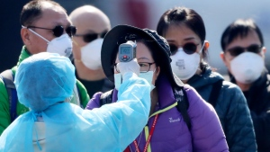 An official in protective suits ensures the temperature of the foreign passengers disembarked from the quarantined Diamond Princess cruise ship before boarding to buses at a port in Yokohama, near Tokyo, Friday, Feb. 21, 2020. (AP Photo/Eugene Hoshiko)