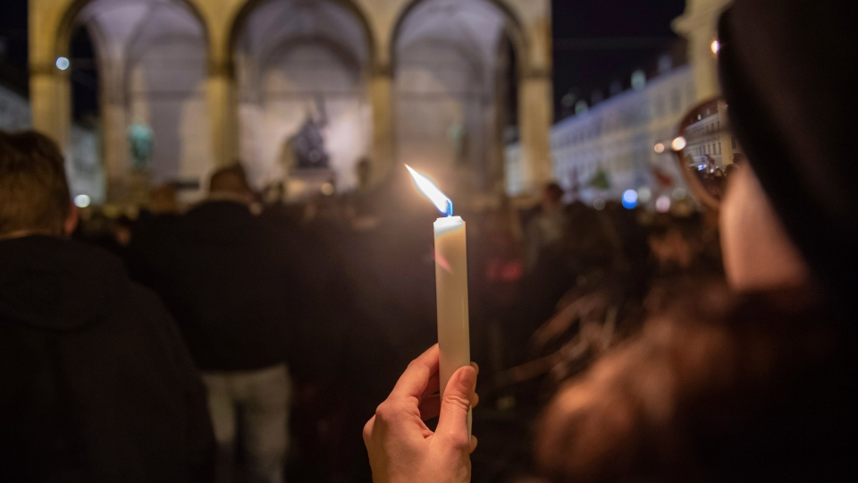 A woman holds a candle during a vigil in Munich city centre, Germany for the victims of the Hanau shooting. (Peter Kneffel/DPA via AP)