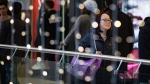 A woman carries a shopping bag during Boxing Day at West Edmonton Mall in Edmonton, on Dec. 26, 2019. (Darryl Dyck / THE CANADIAN PRESS)
