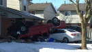 A red pick up truck flipped and crashed into a garage on Jalna Boulevard Friday. (Bryan Bicknell / CTV London)