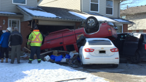 Crews asses the damage to a townhouse after a pickup truck flipped into the garage and vehicles. (Bryan Bicknell / CTV London)