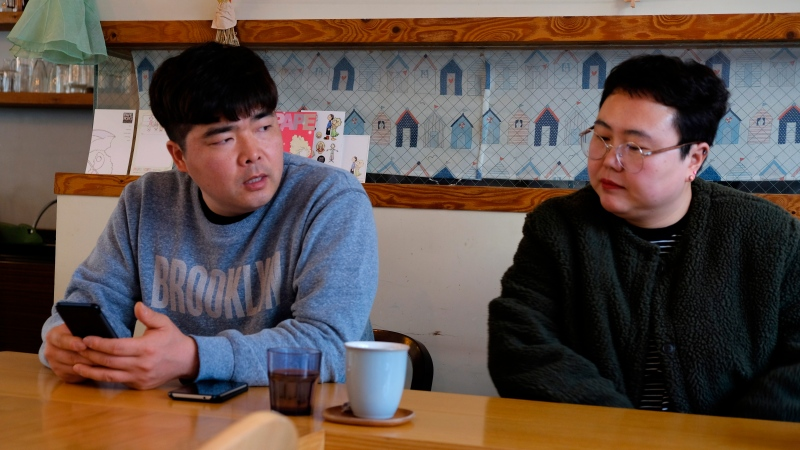 """In this Wednesday, Feb. 19, 2020, photo, props manager Joo Dong-man, left, speaks as costume manager Yang Hee-hwa listens during an interview at a cafe in Ilsan, South Korea. South Korea's latest hit drama """"Crash landing on you"""" portrays the fantastical story of a billionaire heiress accidentally paragliding into North Korea and falling in love with army captain. (AP Photo/Juwon Park)"""